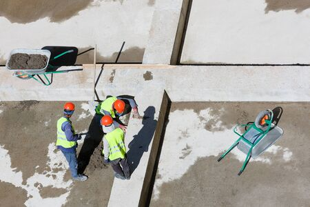 Uniformed workers clean sand on a construction site, top view.