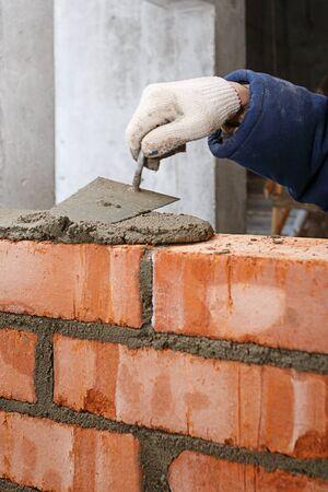 Hand beim Verlegen einer Mauer aus rotem Backstein.