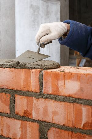 Hand in the process of laying a wall of red brick. Stock fotó - 132040612