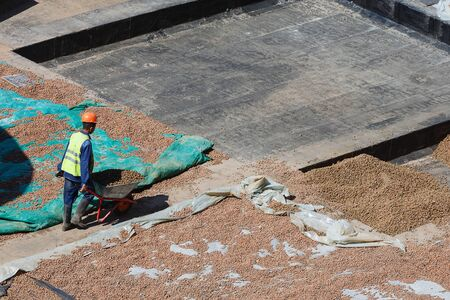 The process of thermal insulation of the roof by workers, by filling with slag. View from above. Archivio Fotografico