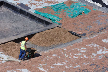 The process of thermal insulation of the roof by workers, by filling with slag. View from above.