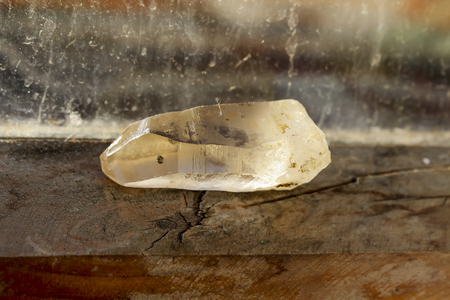 The rock crystal lies on a wooden window sill. Its raining behind the glass  Stok Fotoğraf