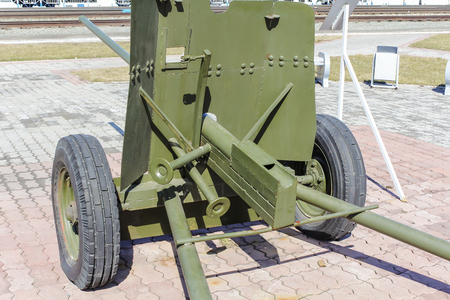 Soviet artillery gun of 1942. Back view. Protective, green color. Stands on the paving slabs.