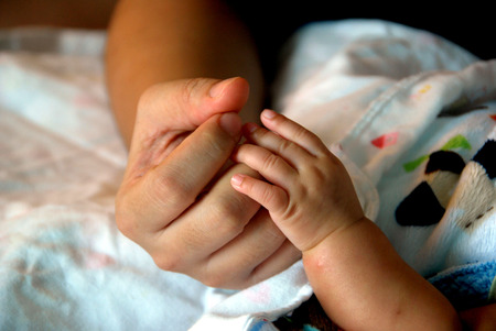 warmly: warmly touch , moms hand with babys hand Stock Photo