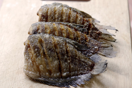trencher: fried snakeskin gourami fish on chopping block