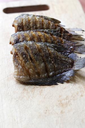 trencher: fried snakeskin gourami  fish on chopping block Stock Photo