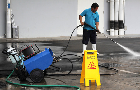 worker cleaning floor with air high pressure machine