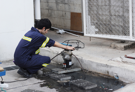 obstruct: engineer used plumbers snake machine to remove clogs that obstruct in main pipe Stock Photo