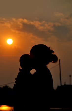 absorb: silhouette of mother and her daughter with sunrise Stock Photo