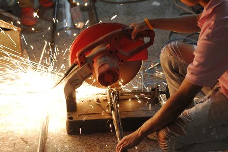 round rods: worker cutting iron pipe by fiber cutting steel machine