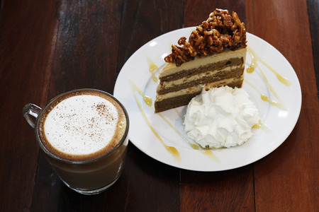 capuchino: hot capuchino with almond coffee cake on wooden table