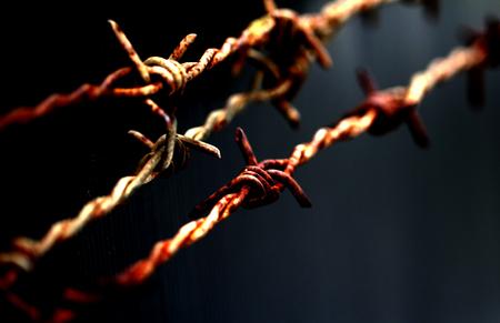 despacio: alambre de púas oxidado con el foco en la lengüeta y borrosa a cabo lentamente en el fondo negro