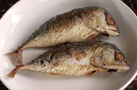closed up Fried short bodied mackerel fishes on white plate .Thai popular food
