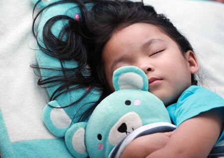 closeup shot of cute little asian girl sleep and hug teddy bear