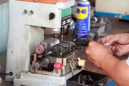 hand of  Locksmith copying car key with key copy machine.Close view of key copying machine with key. Duplicate machine make new key