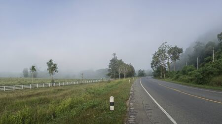 The road between the mountains and the rice fields covered with fog. The road to Pilok Village, Kanchanaburi Province, Thailand.