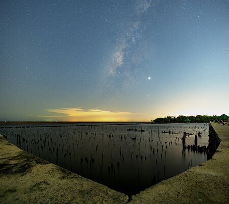 The Milky Way on the night sky with the light reflected from the city lights. The Mangrove forests that only stump. The sea of Samut Sakhon.
