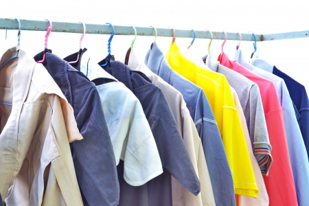 A row of colorful row shirts hanging on hangers on a white background  photo