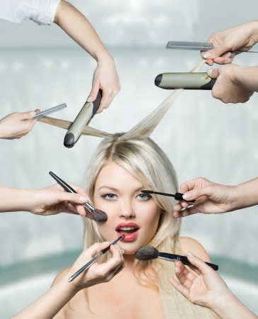 Portrait beautiful white hair girl with makeup brushes near attractive face, many hands apply make up on woman face photo
