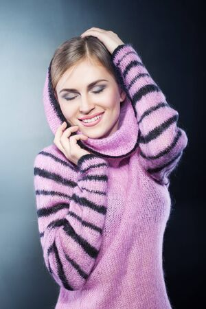 young beautiful smiling girl in a warm pink sweater with black stripe. Stock Photo - 12046294