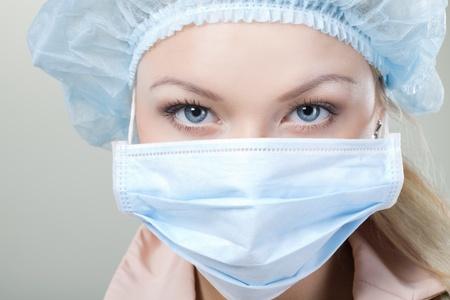 enfermera con cofia: un médico joven. en medetsinskoy gorro y mascarilla