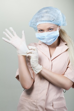 Young nurse in medical gloves and hospital mask on a white background.nurse, girl, gloves, mask, white background photo