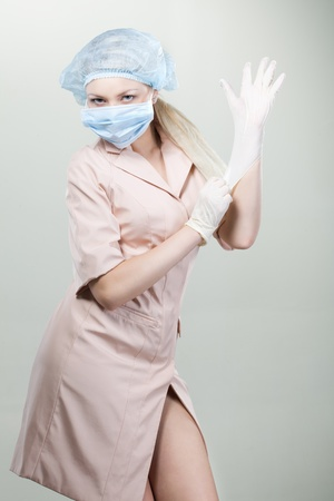 gloves nurse: Young nurse in medical gloves and hospital mask on a white background.nurse, girl, gloves, mask, white background