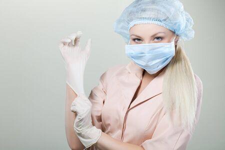 Jeune infirmière dans les gants médicaux et hospitaliers sur un masque background.nurse blanc, jeune fille, gants, masque, fond blanc