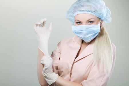 Young nurse in medical gloves and hospital mask on a white background.nurse, girl, gloves, mask, white background