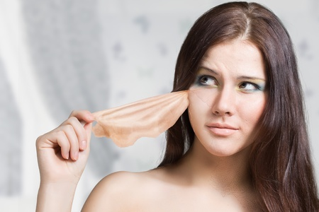 girl takes off the old skin from the face and under her new young Stock Photo - 12195718