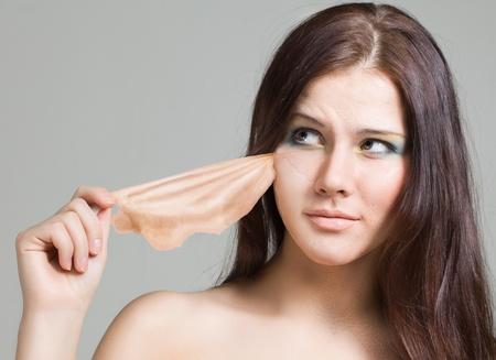 fille enlève la vieille peau du visage et sous son nouveau jeune Banque d'images