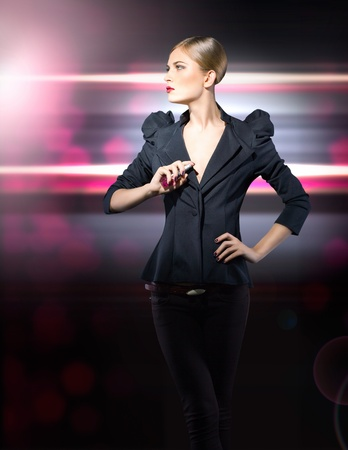 glamorous girl in a black jacket with a bottle of perfume in her photo