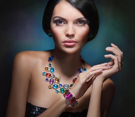 portrait of a glamorous girl with black hair and an expensive necklace with precious and colored stones Stock Photo