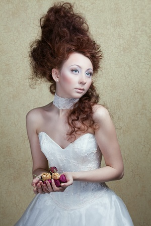 beautiful girl with an unusual hair style in a white dress with rose petals in the hands of