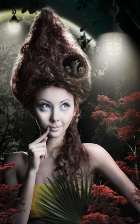 beautiful girl keeper of the forest with a nest with chicks on the head