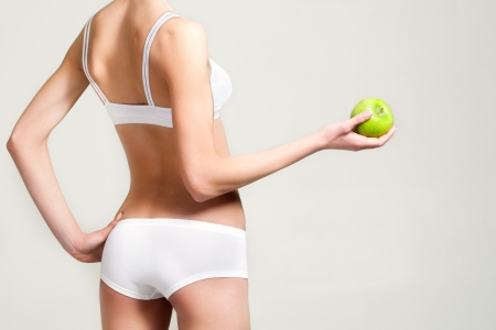 girl in white underwear with a green apple in a cookie photo
