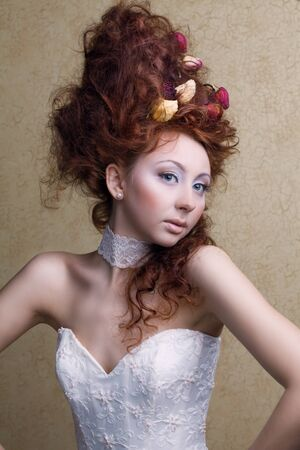 beautiful girl with an unusual hair style in a white dress with rose petals in the hands of photo