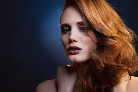 portrait of red-haired girl in a mixed light photo