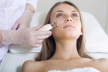 facial massage: femme ayant un traitement stimulant du visage d'un th�rapeute