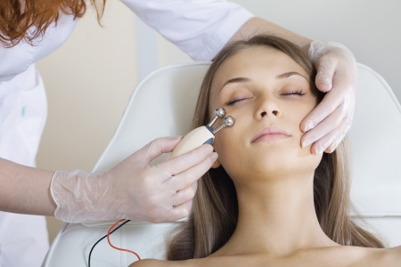 woman having a stimulating facial treatment from a therapist photo