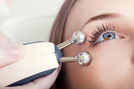 limpieza de cutis: mujer que tiene un tratamiento facial estimulante de un terapeuta