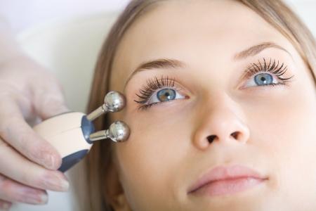 femme ayant un traitement stimulant du visage d'un thérapeute