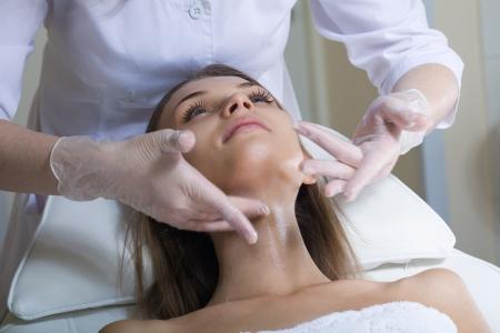 Belle jeune femme recevant un massage du visage avec les yeux fermés dans un centre de spa