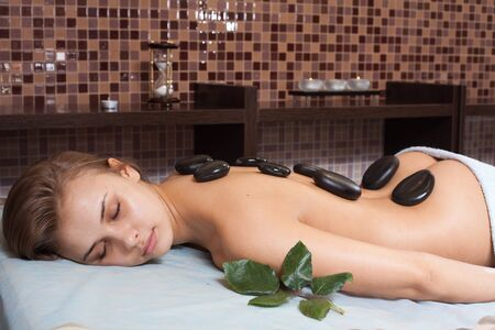 glowing skin:  Glad woman receiving a massage with hot stone in a spa center Stock Photo