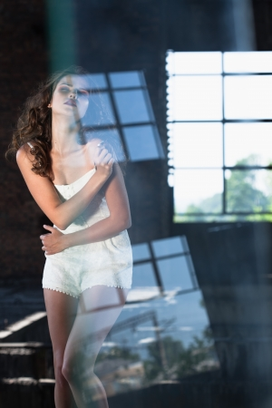 Young gorgeous brunette posing against the backdrop of a building with large windows photo