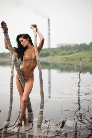 nude slim young woman standing near the pond