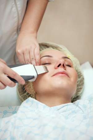 healthier: woman having a stimulating facial treatment from a therapist Stock Photo