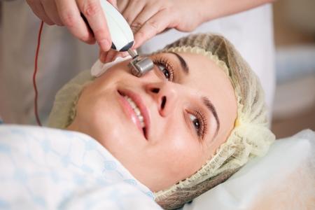 femme ayant un traitement facial stimulant d'un thérapeute