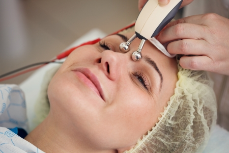 woman having a stimulating facial treatment from a therapist Standard-Bild