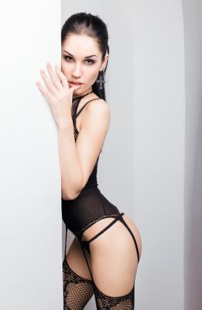 Dame sensuelle posant en lingerie sexy noir pendant l'isolement Banque d'images